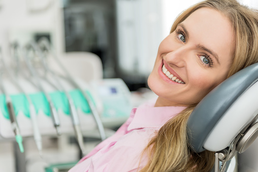 A woman on the dental chair smiling after her cleaning and exam by her Seattle dentist at Pacific Modern Dentistry.