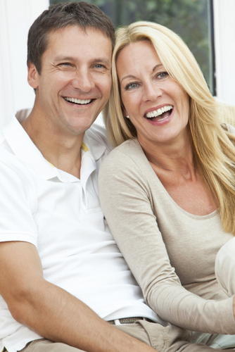 A couple smiling after receiving dental implants at Pacific Modern Dentistry in Seattle, WA