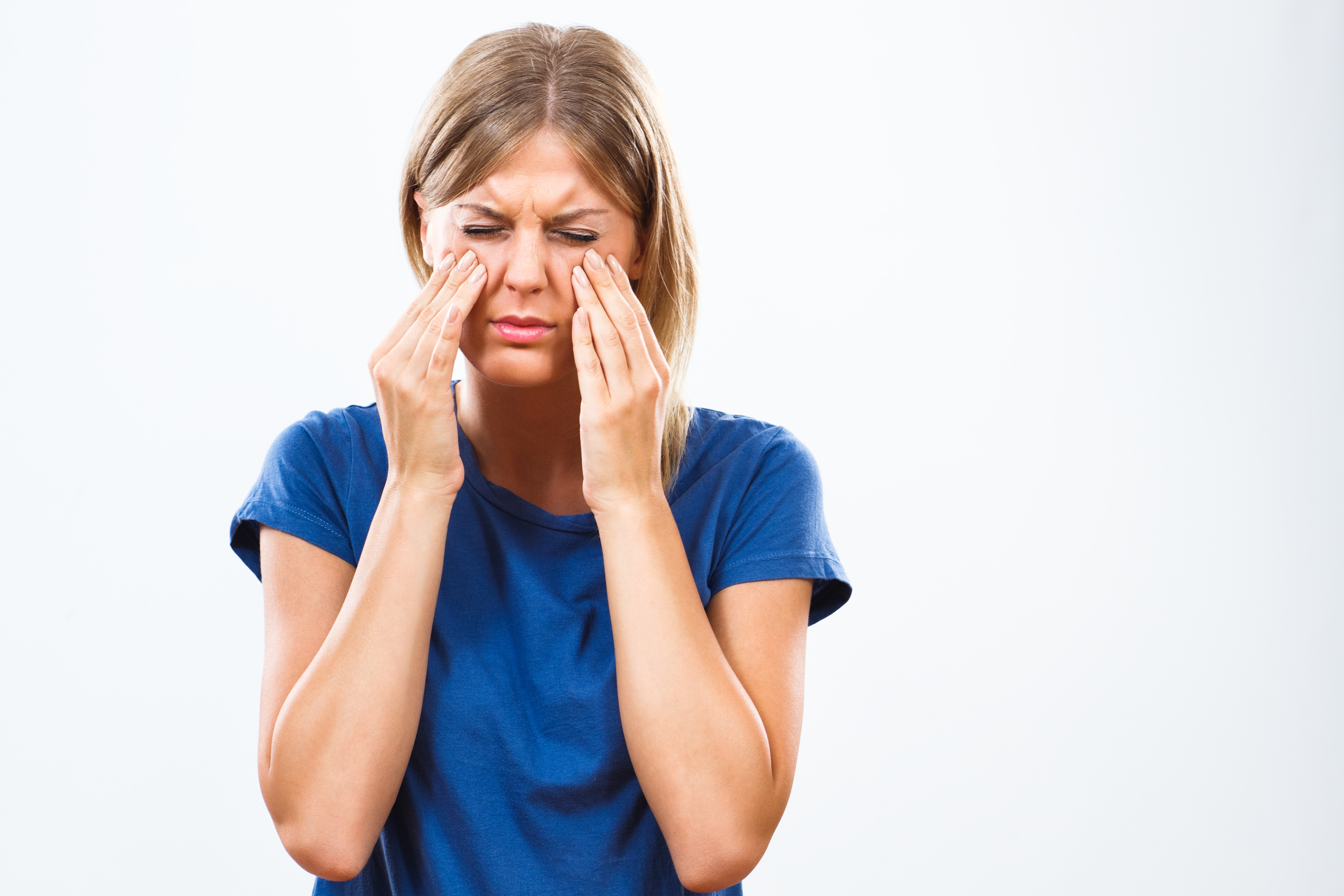 A girl holding her sinus in pain, in need of a sinus lift by Seattle dentist at Pacific Modern Dentistry.